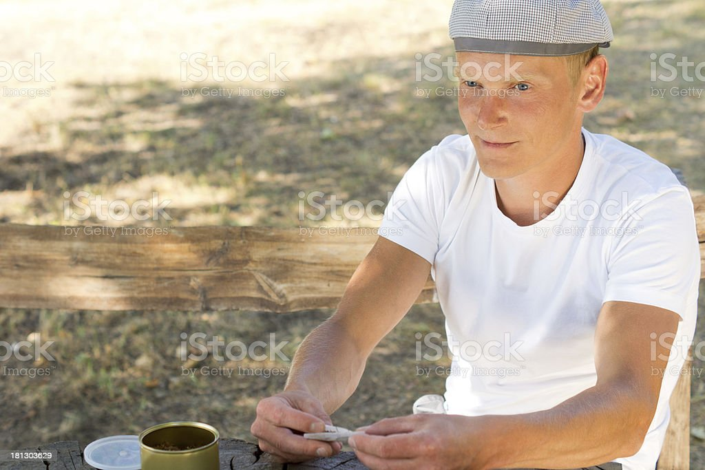 Smoker busy rolling a cigarette royalty-free stock photo