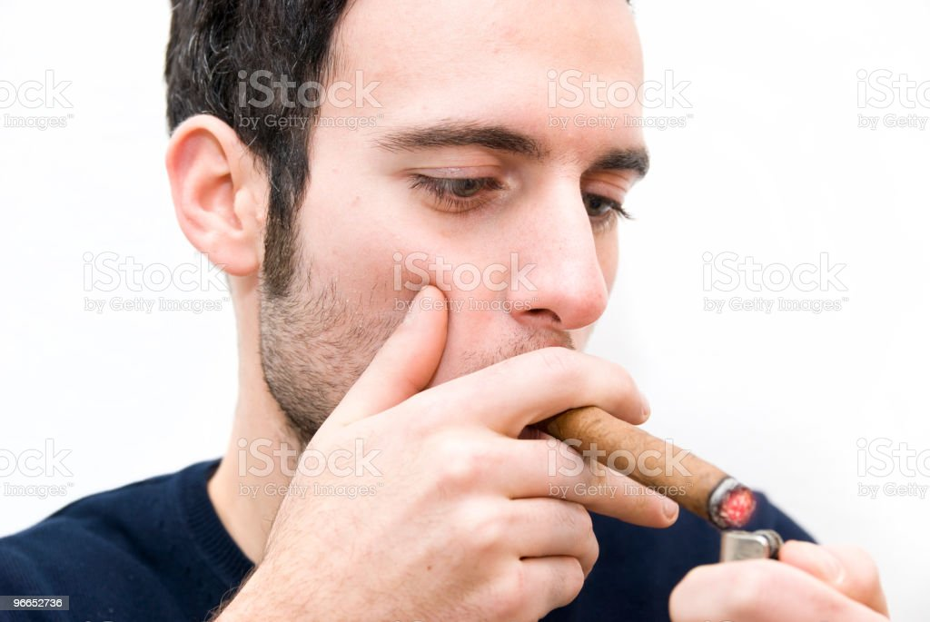 smoker lights up cigar with a lighter royalty-free stock photo