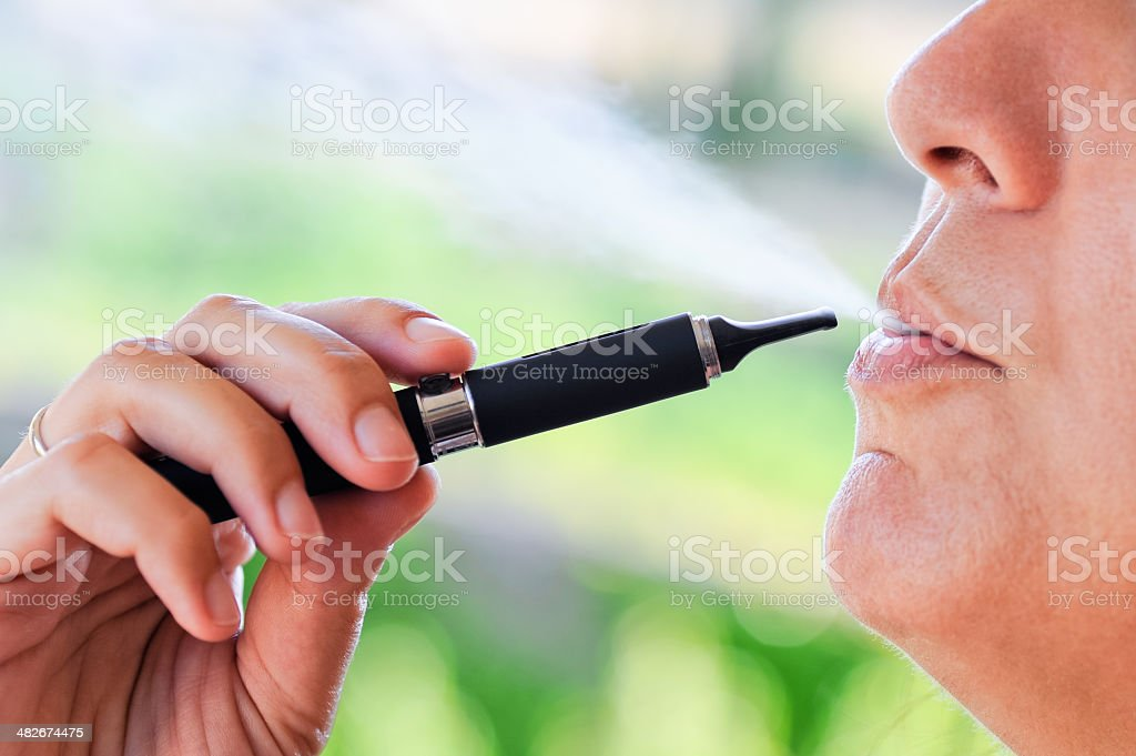 Smoker of Electronic Cigarette with steam stock photo