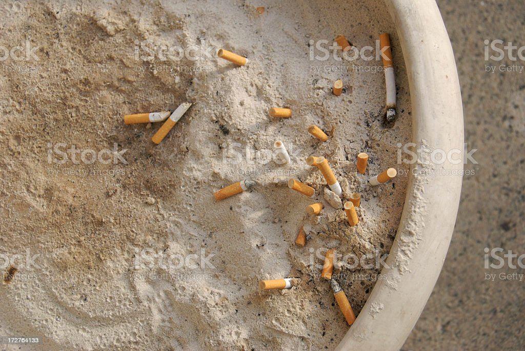 Smokers Club Large Sand Ashtray with Cigarette Butts royalty-free stock photo