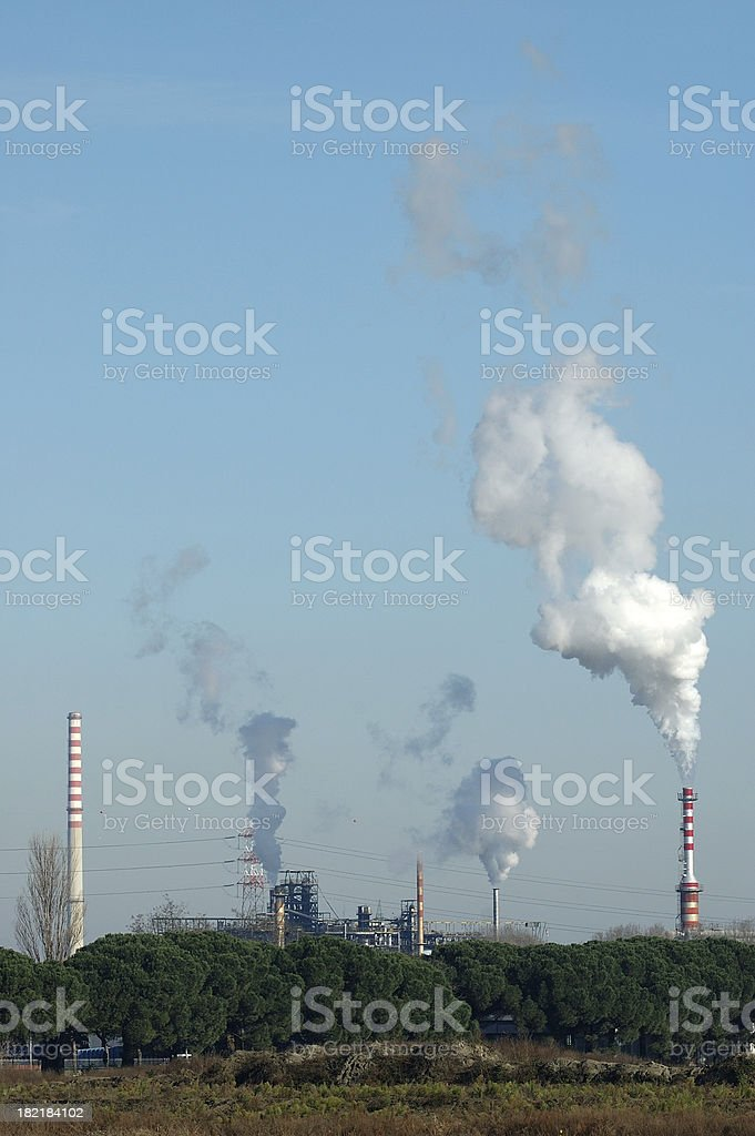 Smokestacks and plumes of smoke against the sky royalty-free stock photo