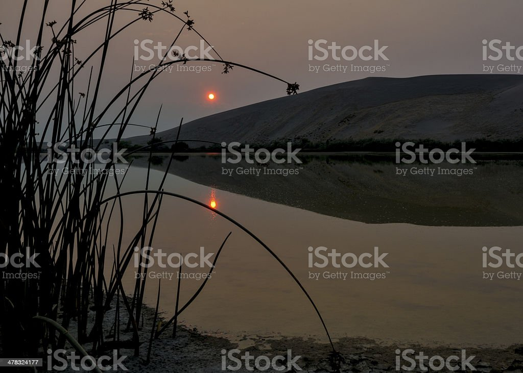 Smokey sunrise over a dester lake with sand dune royalty-free stock photo