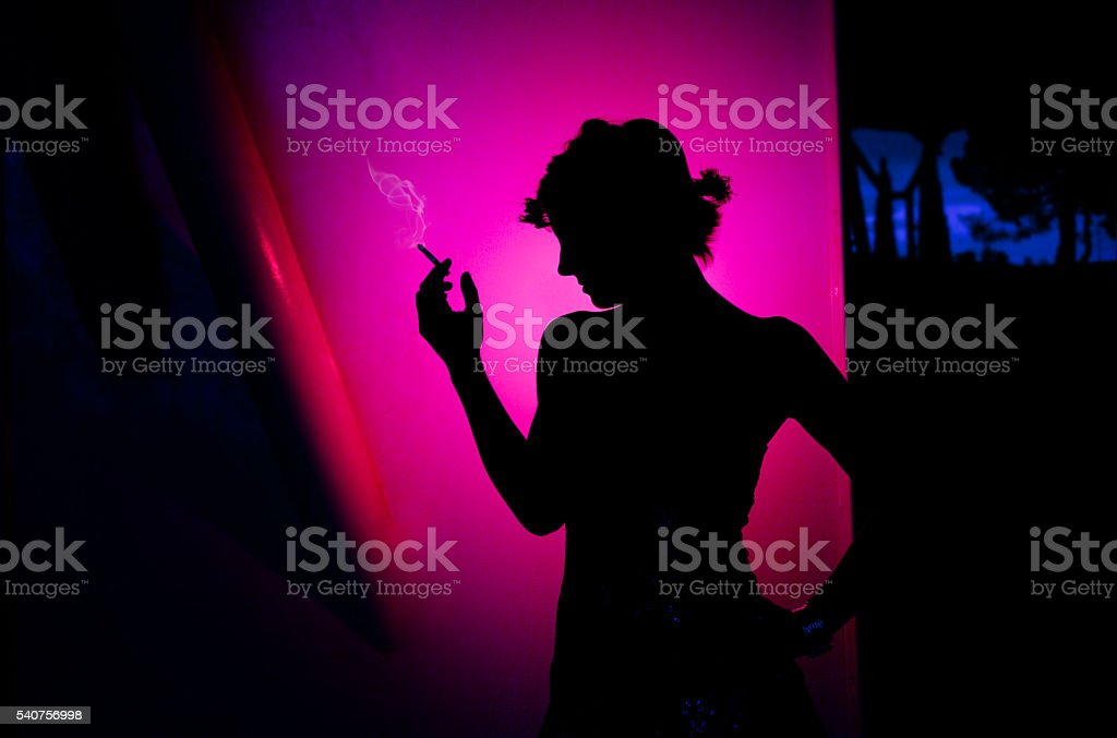 Smoking beautiful woman silhouette on pink background. Lifestyle, Fashion woman. stock photo