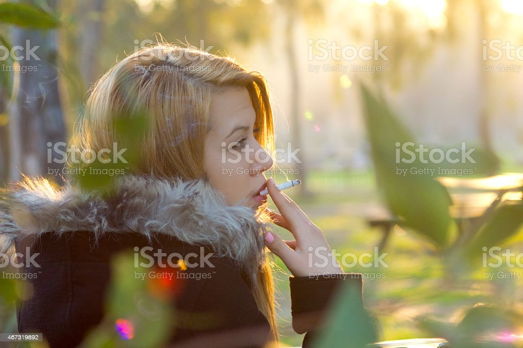 smoking beautiful young woman stock photo