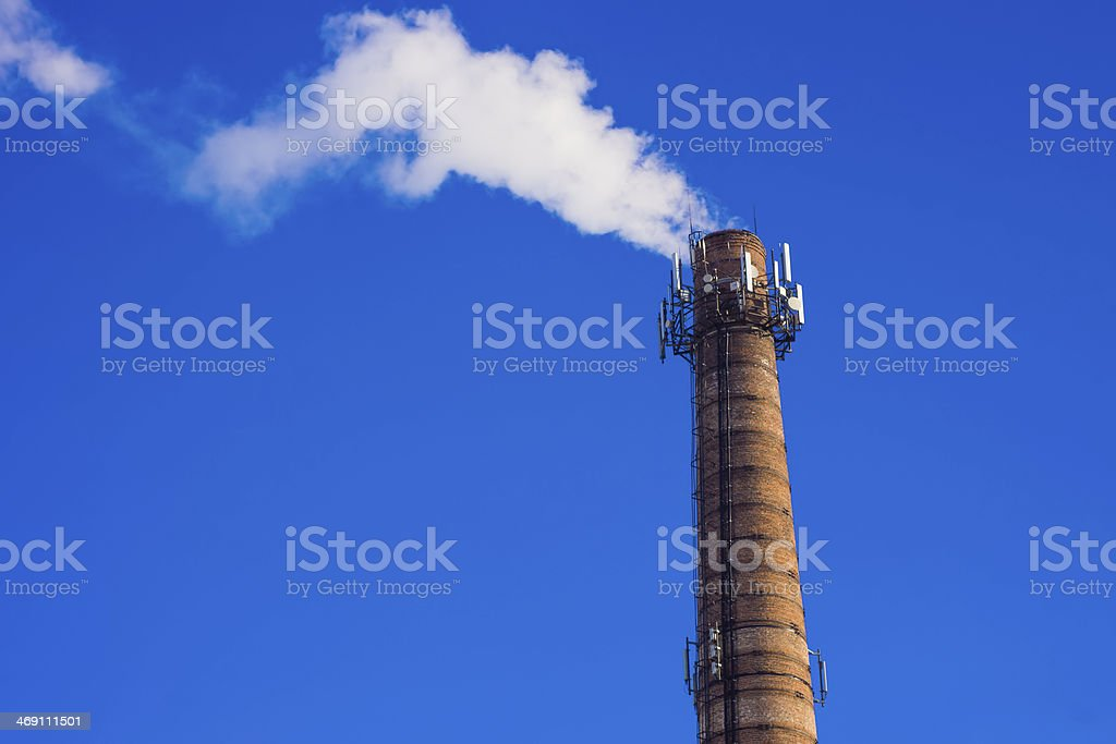 Smoking brick tower with mobile antenna on top stock photo