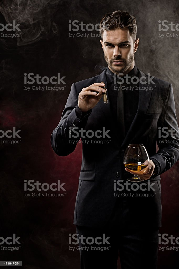 smoking cigar and drinking whiskey well dressed man stock photo