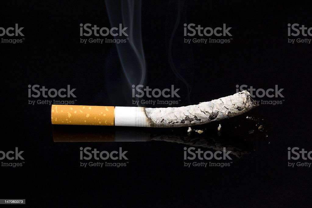 Smoking cigarette against a dark background. royalty-free stock photo
