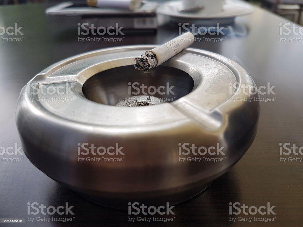 smoking cigarette on ashtray stock photo