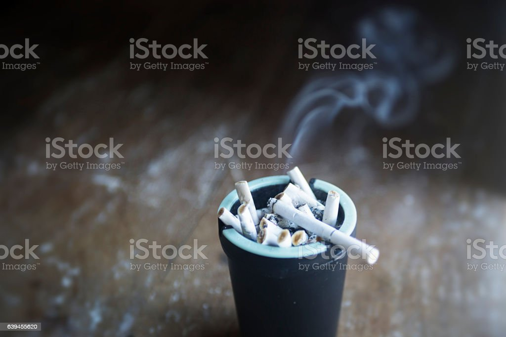 Smoking cigarettes in an ash tray stock photo
