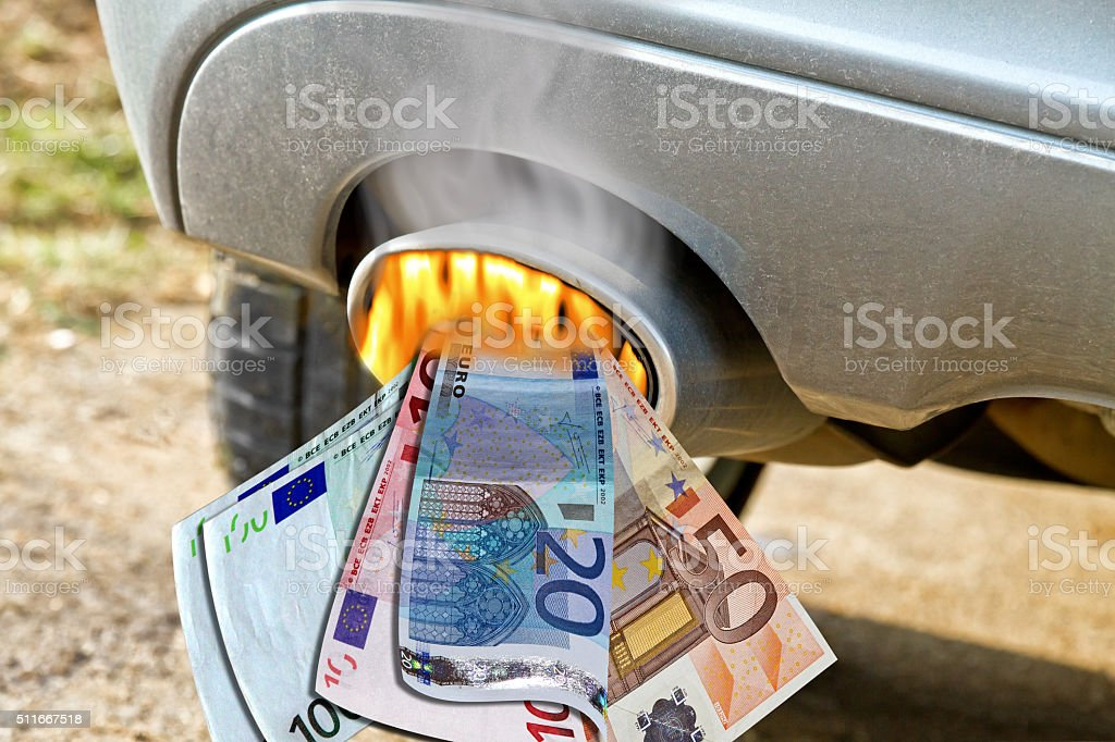 Smoking exhaust pipe with burning money stock photo