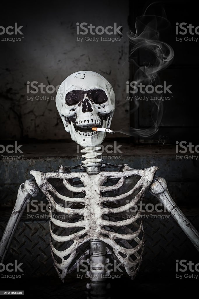 Smoking human skeleton with cigarette stock photo