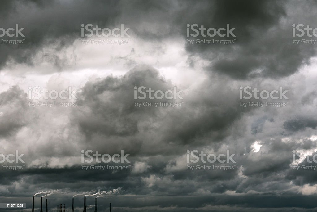 Smoking industrial pipes against background of thunderclouds royalty-free stock photo
