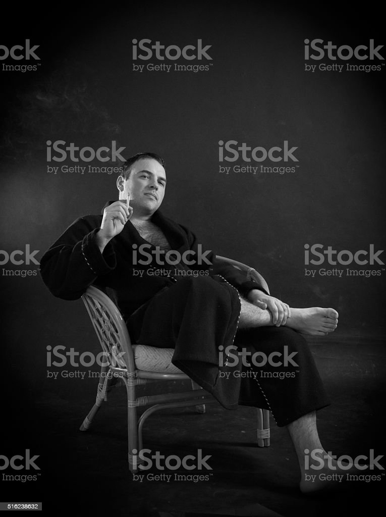 Smoking man in a dressing gown stock photo