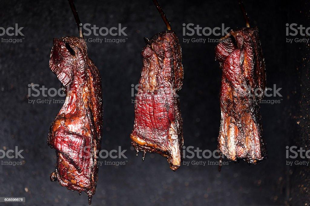 Smoking pork neck in home smokehouse stock photo