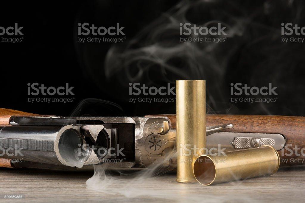 Smoking rifle and brass shells stock photo