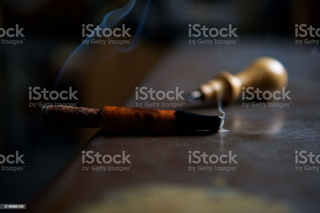 smoking Toscano cigar with mouthpiece in briar and awl blur stock photo