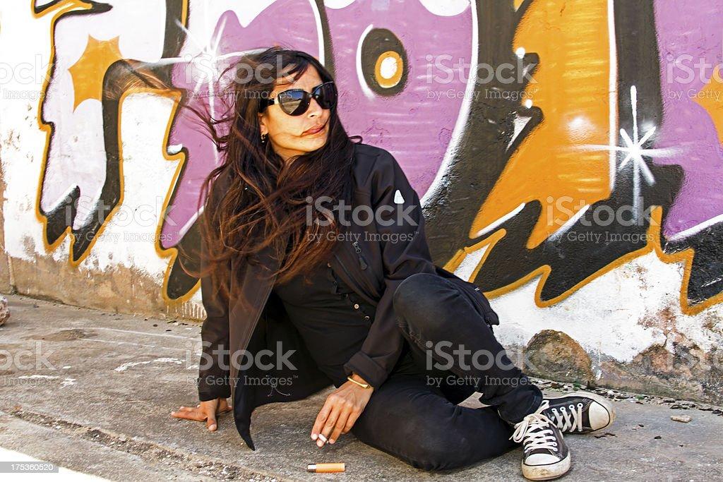 Smoking woman in black at the graffiti brick wall royalty-free stock photo
