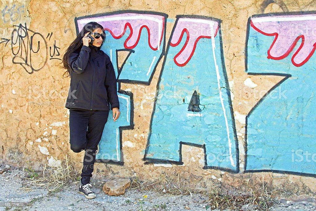 Smoking woman phoning at a graffiti wall royalty-free stock photo