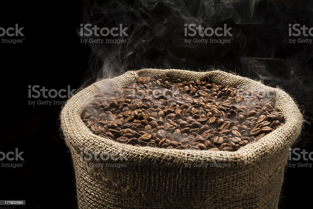 Smoky, hot coffee beans in the sack. royalty-free stock photo