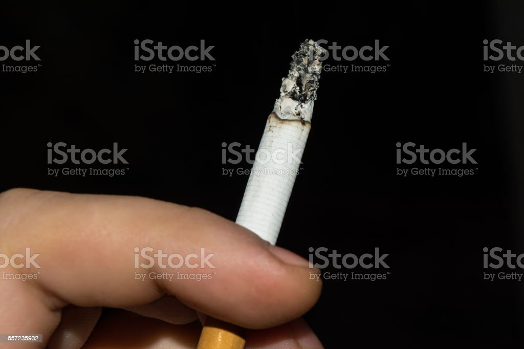 Smoldering cigarette sandwiched between male fingers, black background stock photo