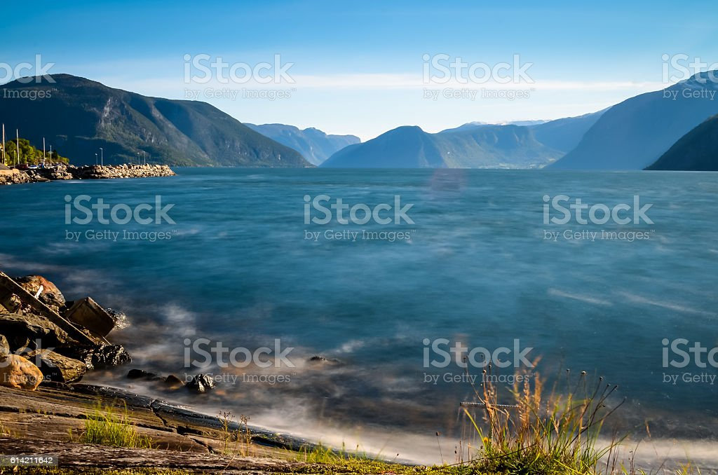 smooth and blue water at norwegian fjord, autumn stock photo