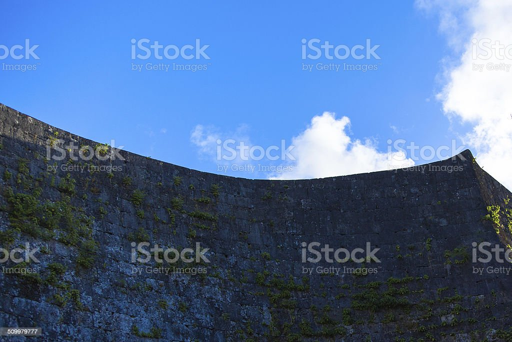 Smooth curve rampart of Shuri Castle and blue sky stock photo