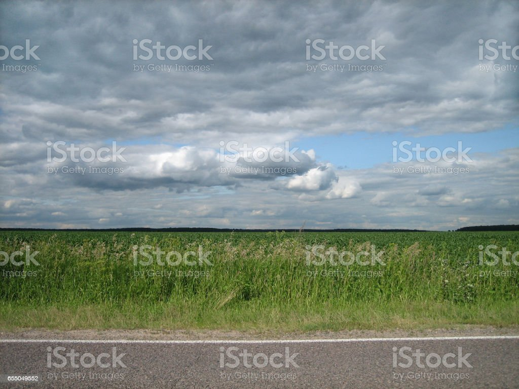 Smooth edge of paved roads in a clean green field in the countryside. stock photo