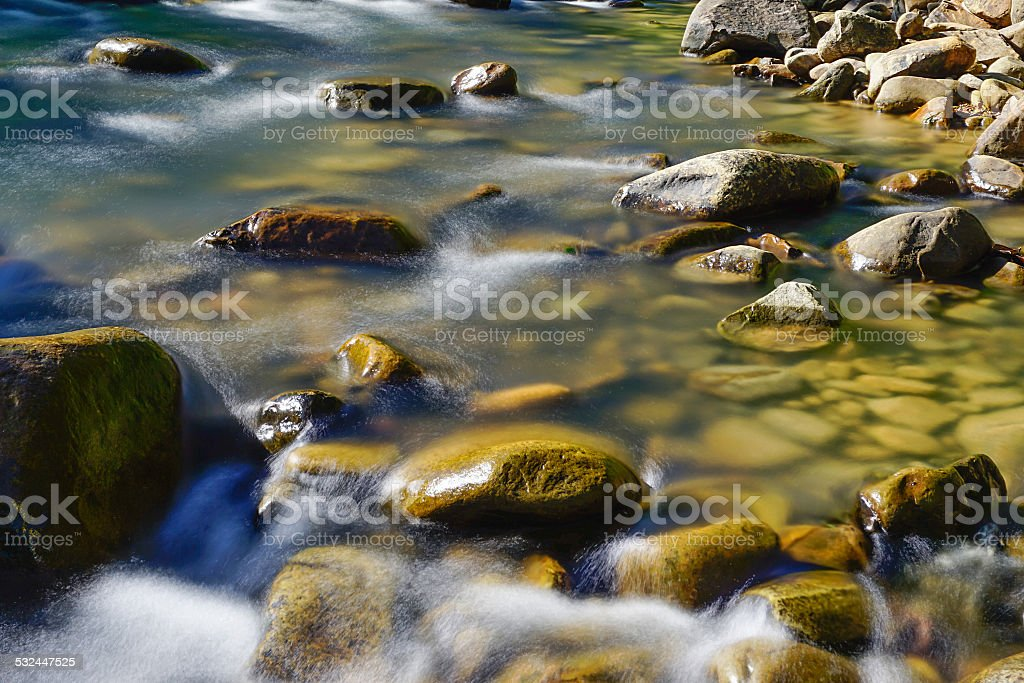 smooth flowing water at rocky river stock photo