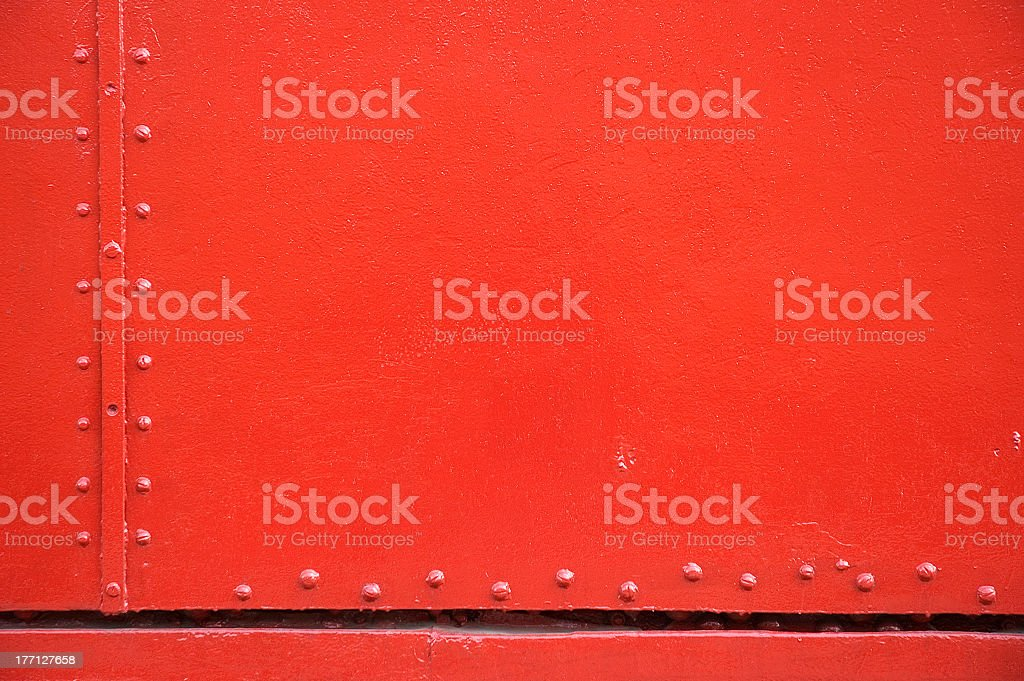 Smooth red metal surface with panel joins and rivets stock photo