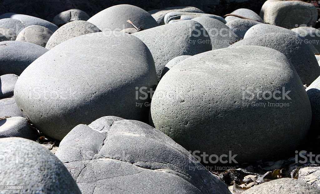 Smooth round stones on seashore royalty-free stock photo