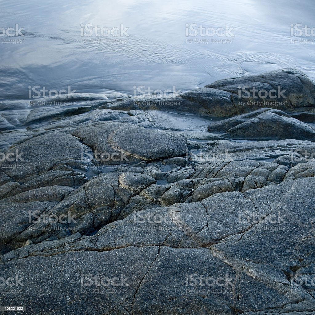 Smooth Sand Stone Beach at Water's Edge stock photo