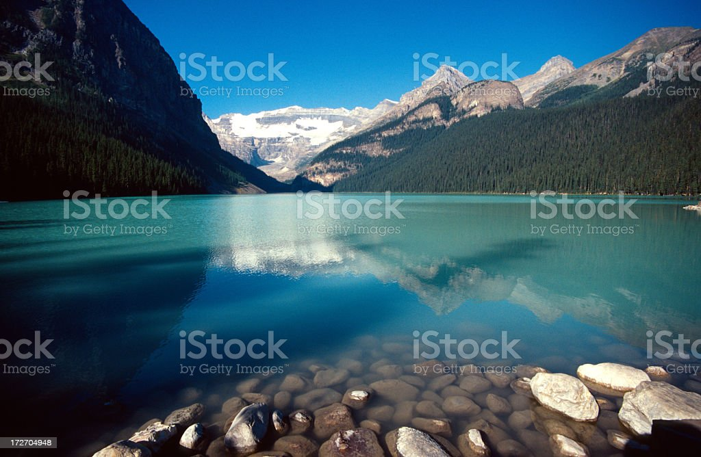 Smooth stones and still waters of Lake Louise in Banff stock photo
