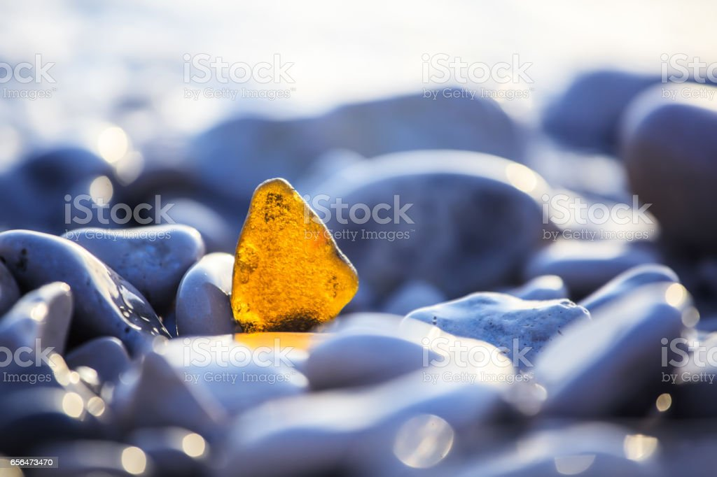 Smoothed glass.... in the background out of focus pebble beach. stock photo