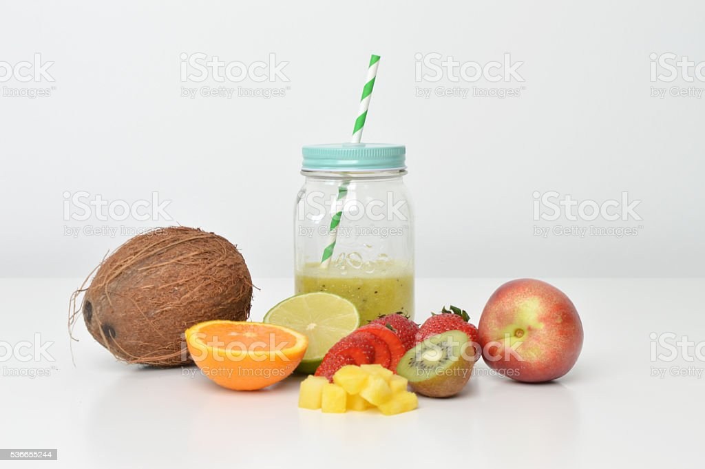 Smoothie jar with a straw and fruits stock photo