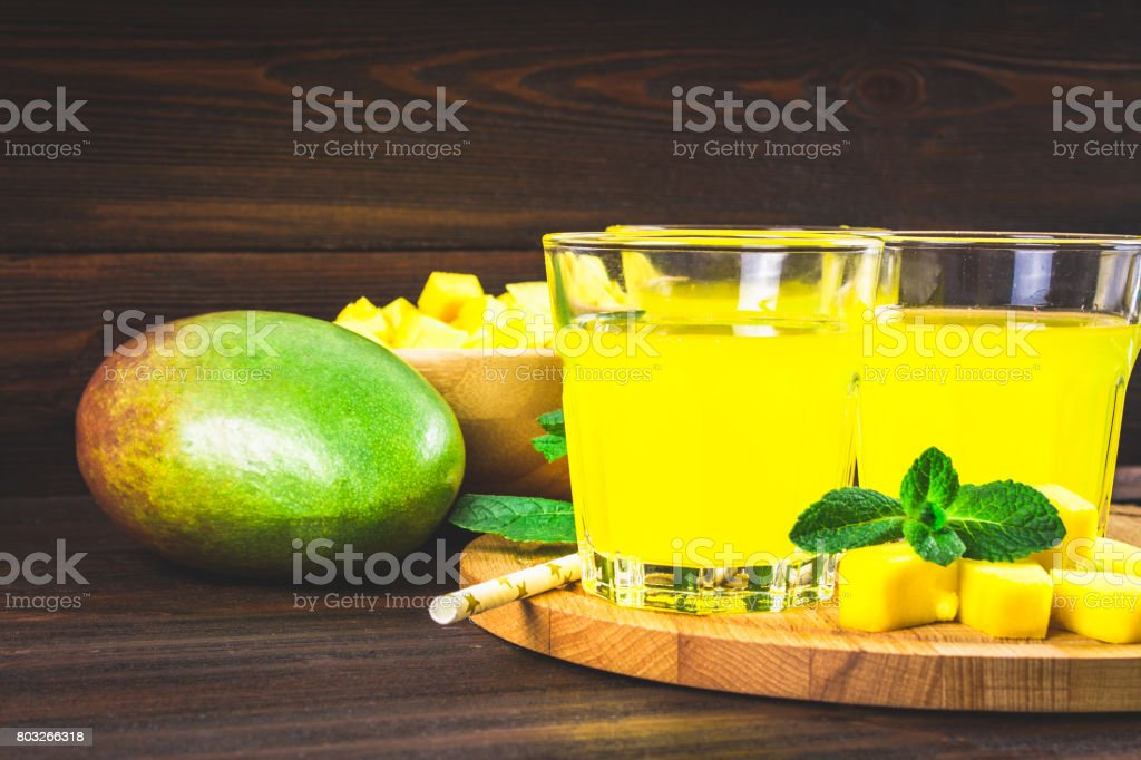 Smoothies mango with straw and mint in a glass beaker. Plate wit stock photo