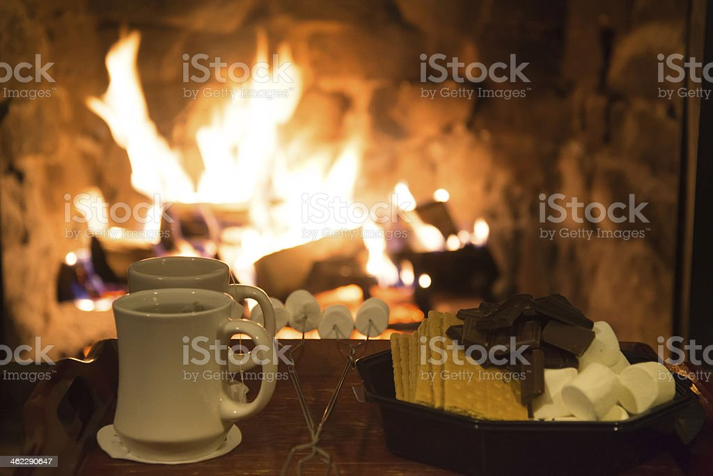 Smores treats and hot tea in front of a fireplace stock photo