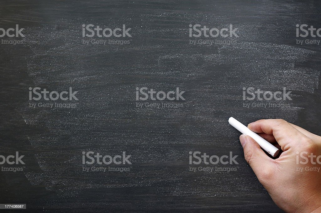 Smudged blackboard with a hand holding chalk stock photo