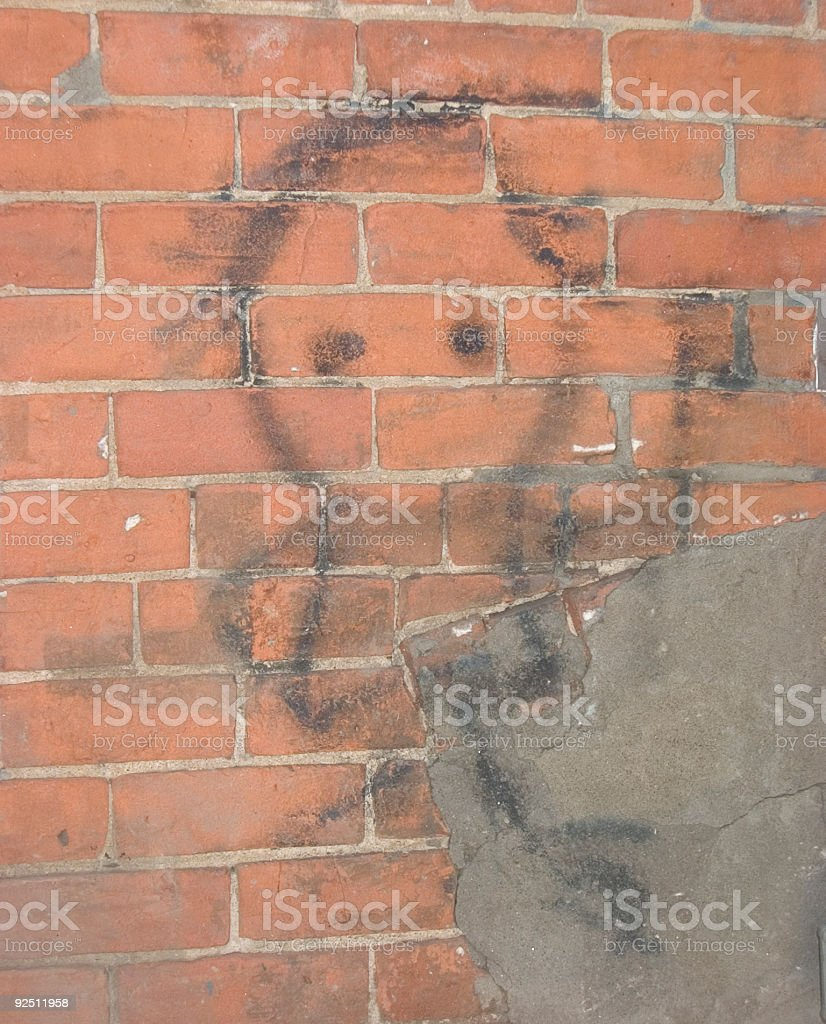 smudged figure on brick wall stock photo