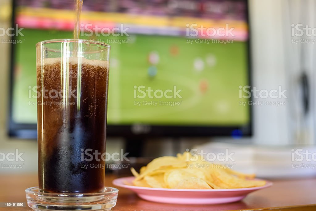 Snack at time watching football on live Television. stock photo