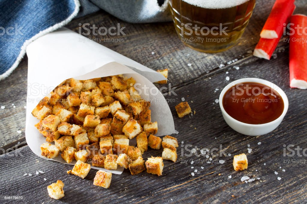 Snack food. Crab crackers, dried white bread and crab sticks and tomato ketchup on the wooden table. stock photo