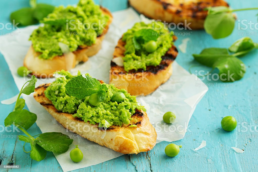 Snack of peas and mint with toast. stock photo