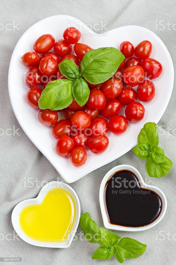 Snack tomatoes, basil, oil and vinegar to make healthy salad stock photo