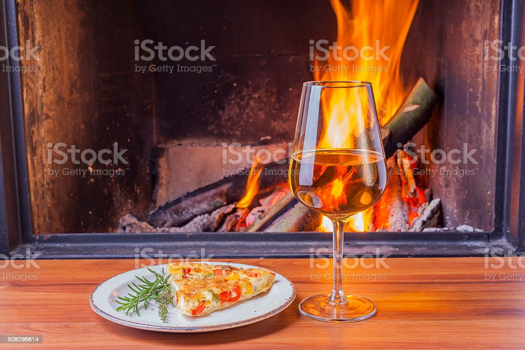 snacks and wine at cozy fireplace stock photo