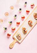 Snacks, brushetta sandwiches, gazpacho shots, desserts over pastel pink background