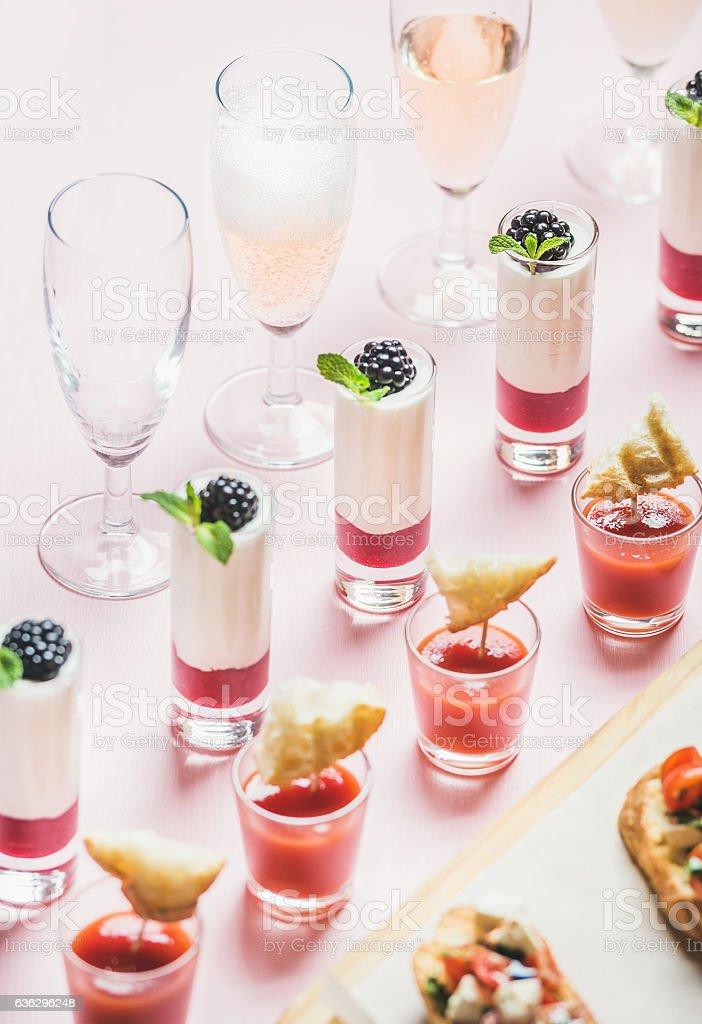 Snacks, brushetta sandwiches, gazpacho shots, desserts over pastel pink background stock photo