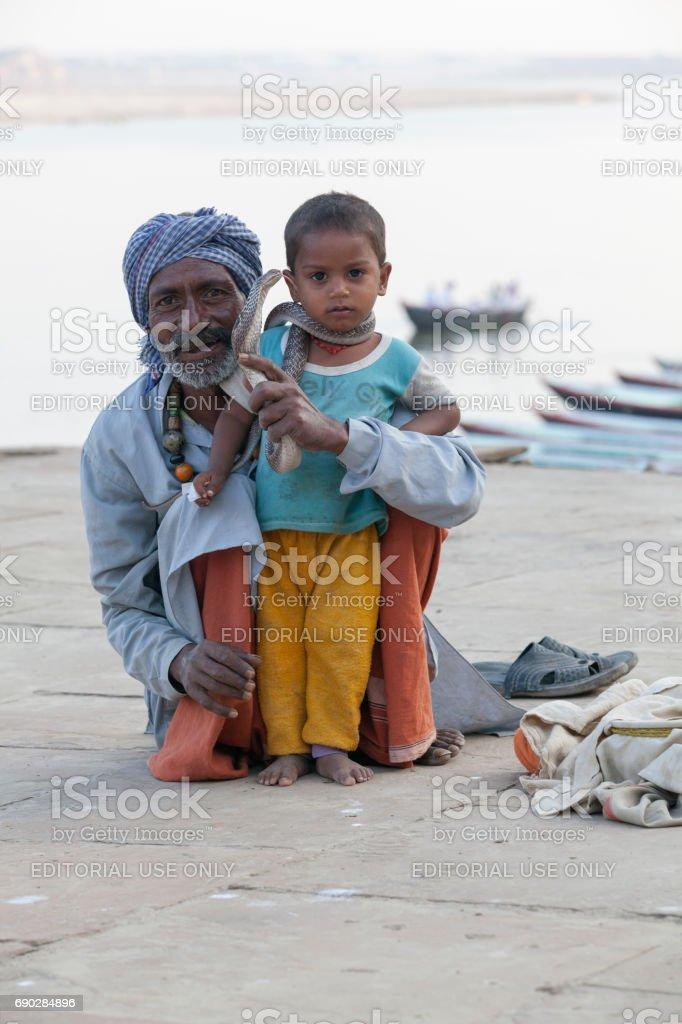 India, Varanasi - November 2009: snake charmer and a little boy posing with cobra stock photo