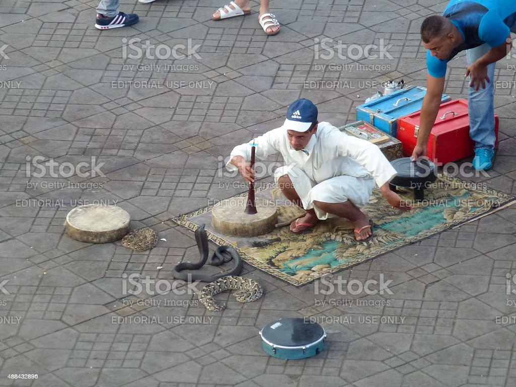 Snake charmer working at Djemaa el Fna square in Marrakech. stock photo