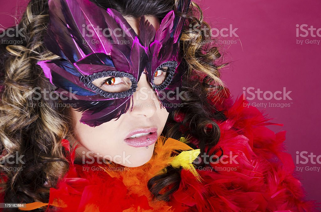 Snarling woman in bird mask and feathers. stock photo
