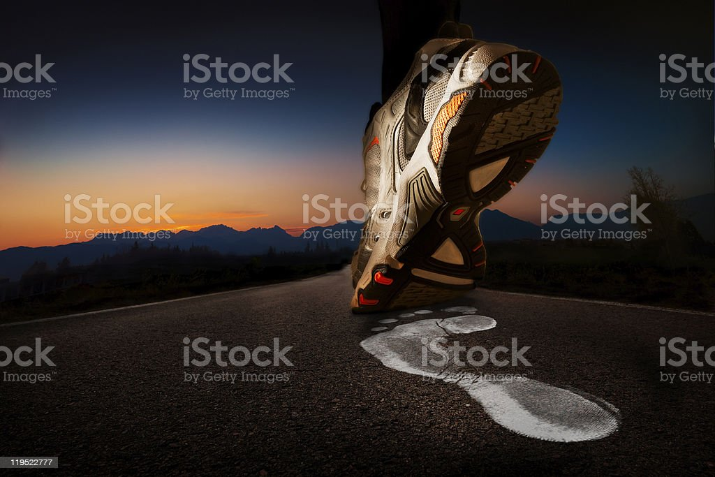 Sneaker and white footprint on asphalt at dawn stock photo