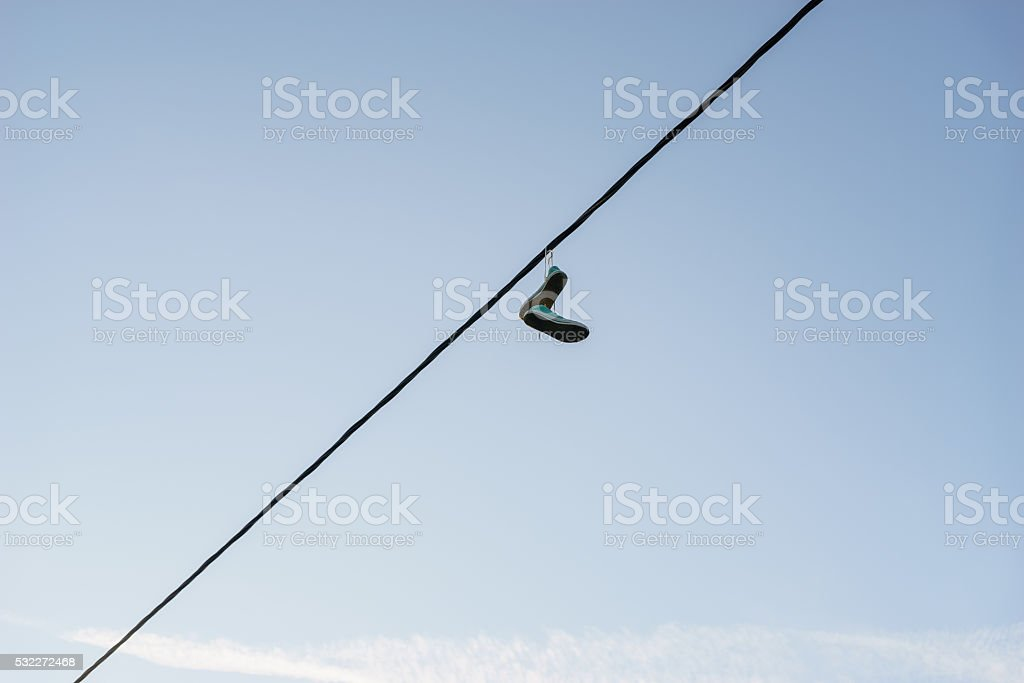 Sneakers dangling on power line cable stock photo